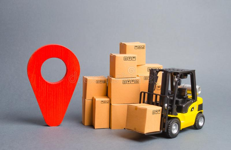 Gul gaffeltruck med kartonger och ett rött positionsstift Lokalisera packar och gods Spåring av jordlotter via internet royaltyfri bild