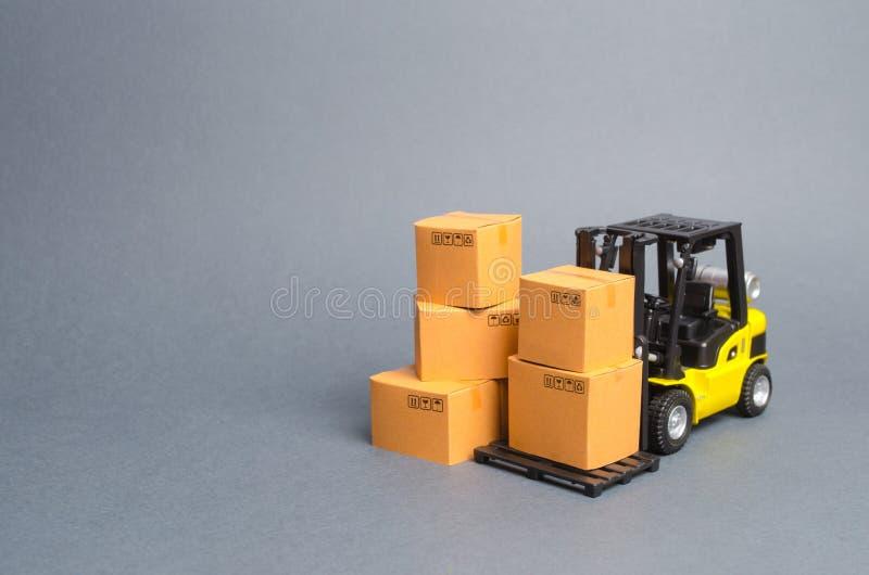 Gul gaffeltruck med kartonger Servicelagring av gods i ett lager, en leverans och trans. Niv? och en grupp av askar p? en vit bak royaltyfri bild