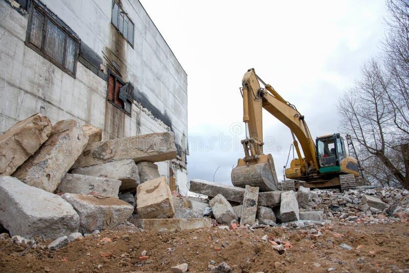 Gul grävmaskin med hink vid rivning av hög byggnad Hydrauliska maskiner för rivning Backhoe förstör betong från det gamla royaltyfri fotografi