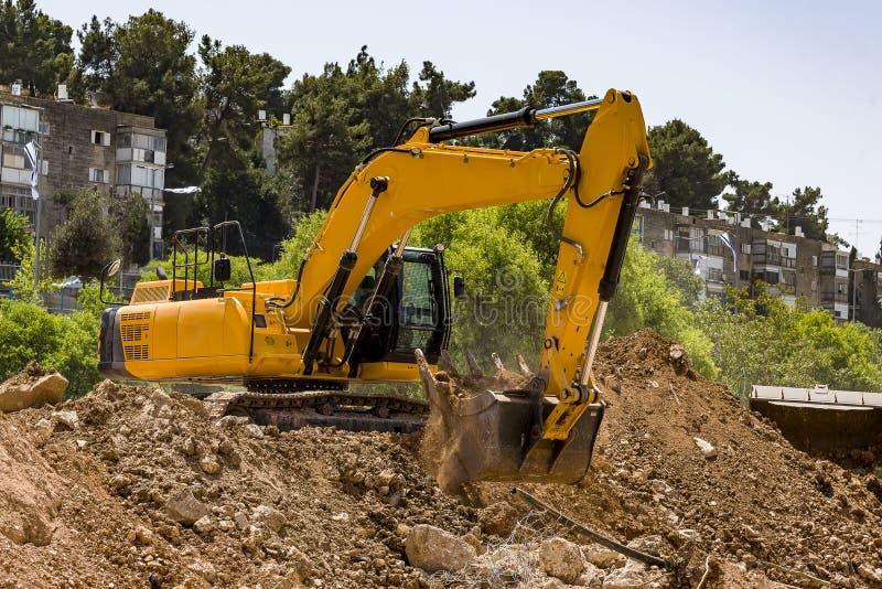 Gul grävskopamaskin med den uppstigna bangkonstruktionsplatsen arkivfoto