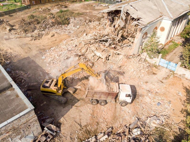Gul grävskopapäfyllning ut rackar ner på och skräp in i dumper arkivfoto