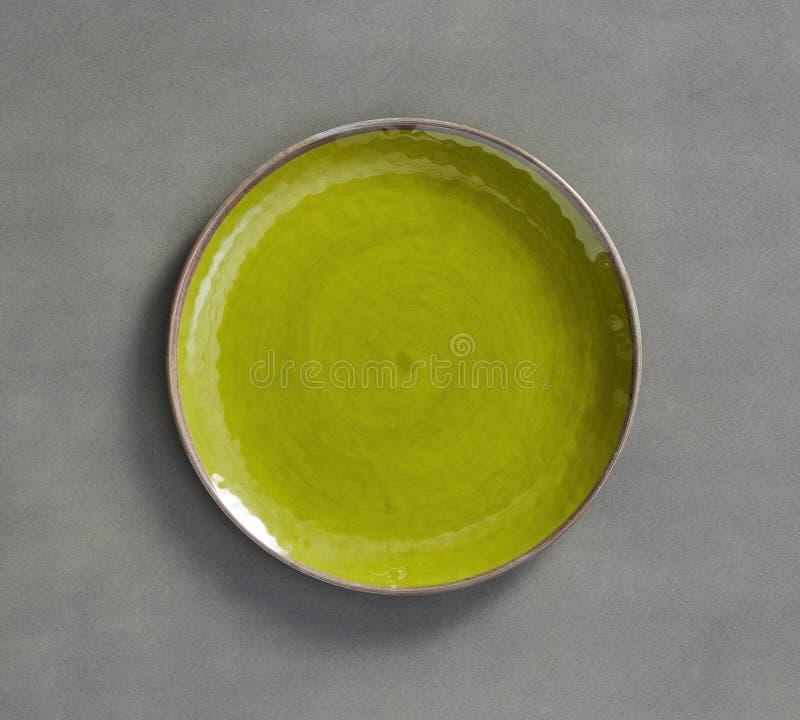 Gul grön virvelMelamineplatta med ljust - grå bakgrund arkivbild