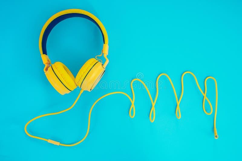Gul hörlurar eller hörlurdator på en blå pastellfärgad bakgrund arkivbild
