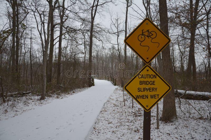 Gul hal varningsbro när vått tecken på bron med snö royaltyfri foto