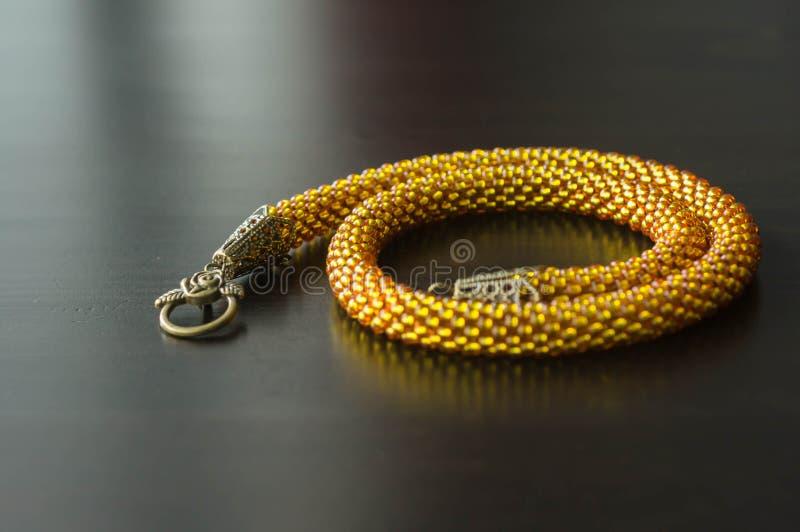 Gul halsband från pärlor på en mörk yttersida arkivfoton