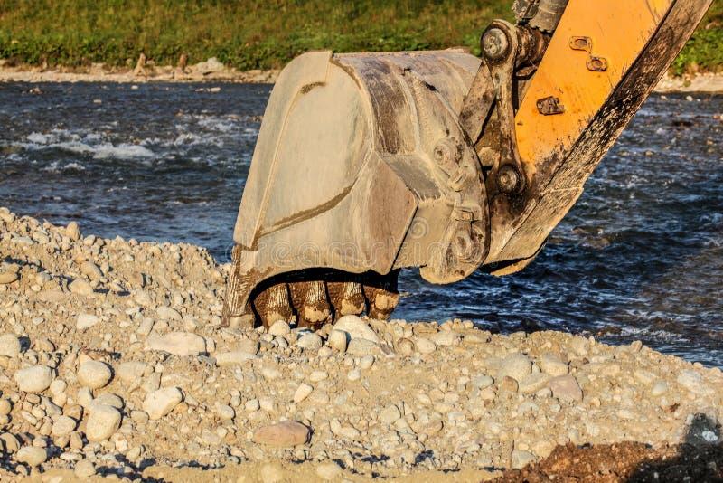Gul hink för grävaregrävskopamaskin som gräver i stenar som är jord vid floden royaltyfri foto