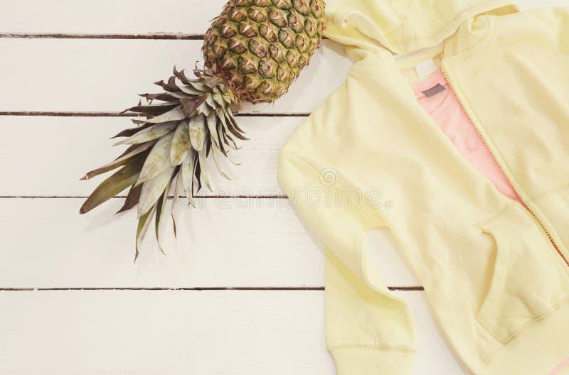 Gul Hoodie och en T-tröja, ananas Vit gammal träbakgrund royaltyfri bild