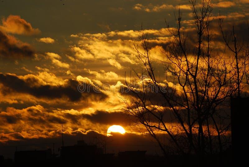 Gul inställningssol för mörka moln arkivbild