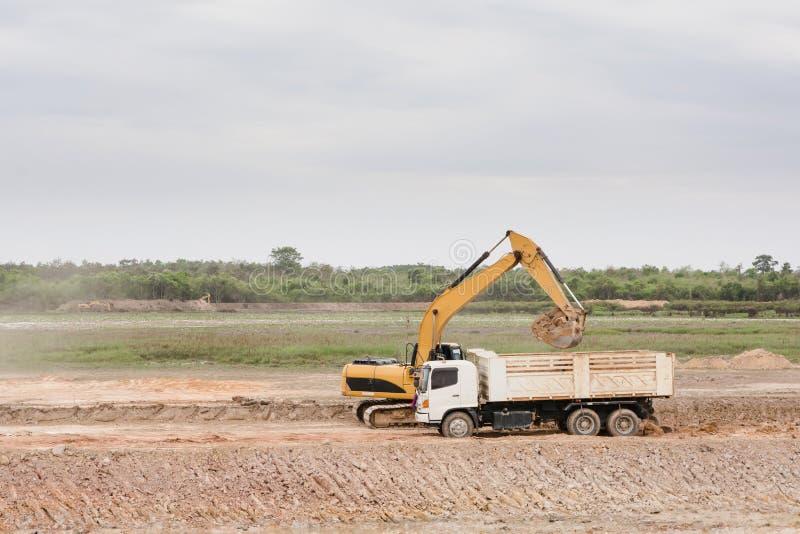 Gul jord för grävskopamaskinpäfyllning in i en dumper på const royaltyfri fotografi