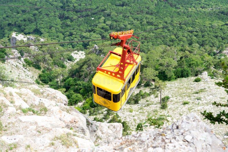 Gul kabin för kabelbil ovanför skogen på berget arkivfoton