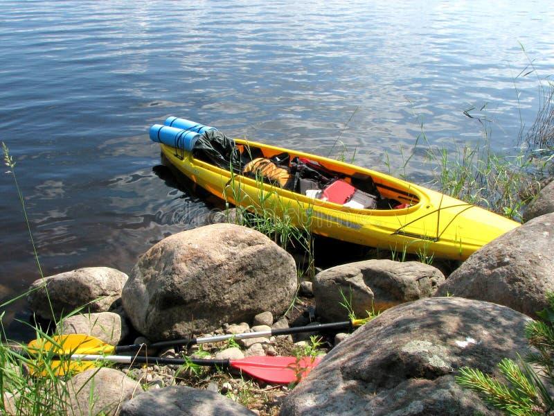 Gul kajak med saker och skovlar på en sjö på en stenig kust royaltyfri foto