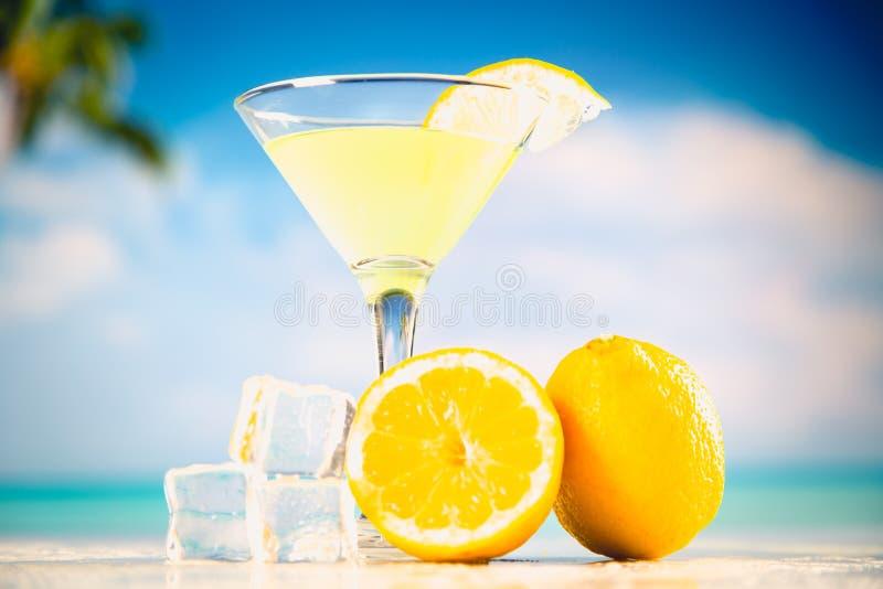 Gul kall drink på en strand med citronen och is arkivfoton