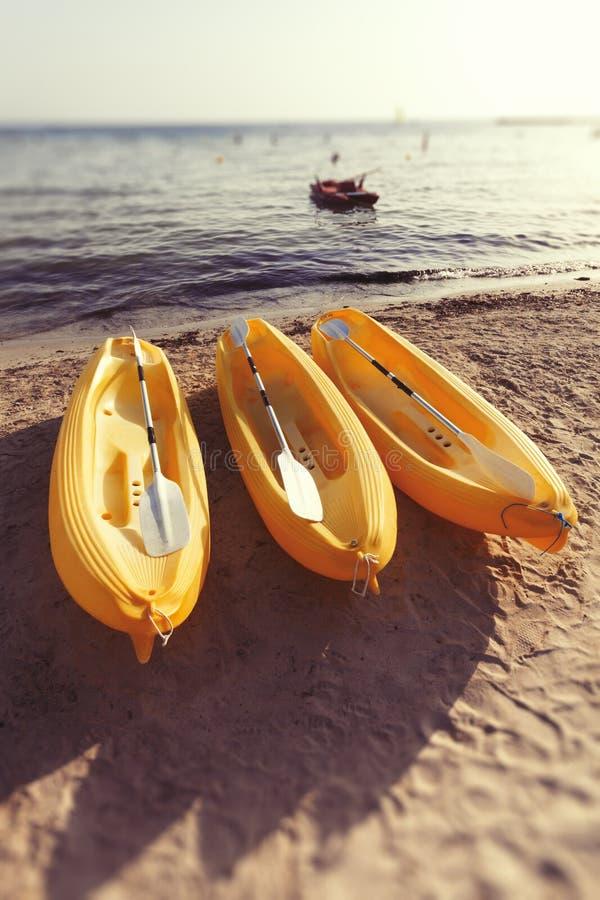 Gul kanot för tre plast- på stranden på havet Sommar arkivfoton