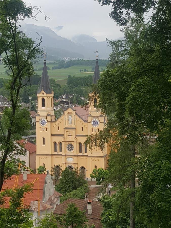 Gul katholic kyrka i brunico arkivfoto
