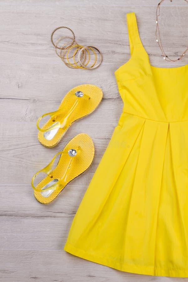 Gul klänning med sandaler och bijouterie royaltyfri fotografi