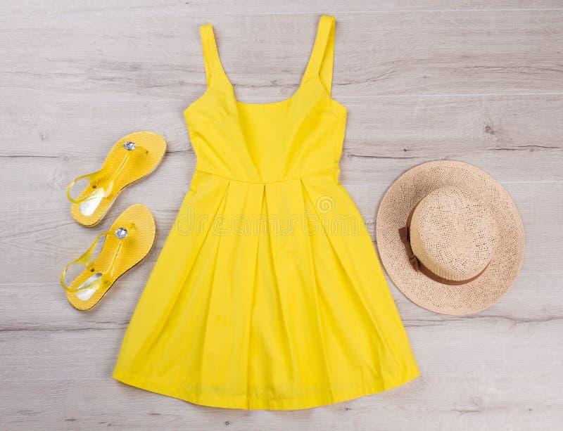 Gul klänning med sandaler och hatten royaltyfri bild