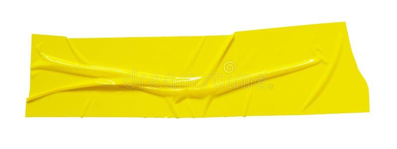 Gul klibbig tejp Sönderrivet skrynkligt tejpstycke som isoleras på vit bakgrund arkivfoton