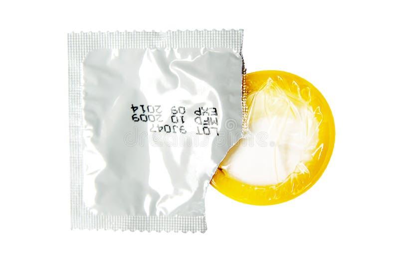 Gul kondom med den öppna packen arkivbild