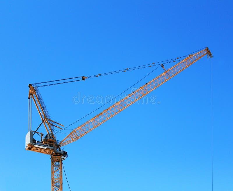 Gul konstruktionskran med blå himmel royaltyfria foton