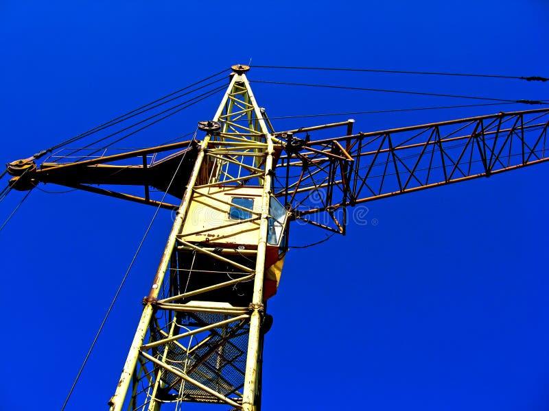 Gul konstruktionskran på bakgrunden av en blå himmel arkivbilder