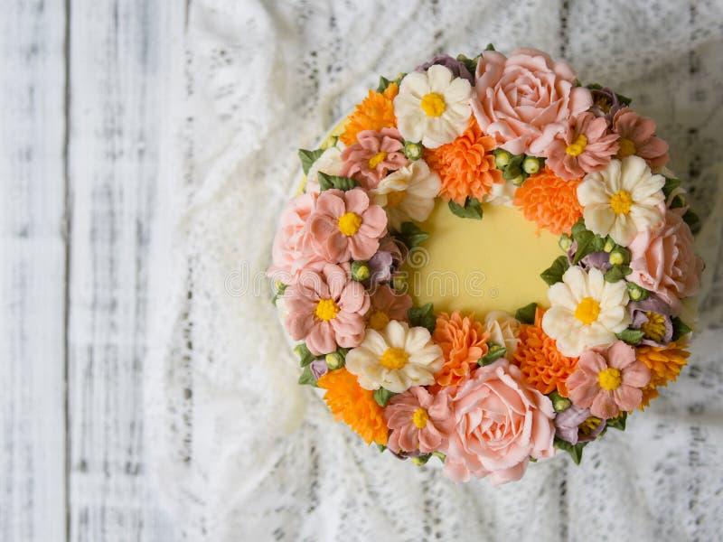 Gul kräm- kaka som dekoreras med buttercreamblommor - pioner, rosor, krysantemum, scabiosaen, nejlikor - på vit träbaksida fotografering för bildbyråer