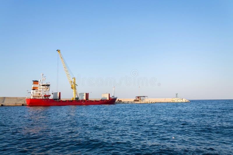 Gul kran som lastar av sand från det stora fraktbåtlastfartyget i hamnen, fraktdigitalization, trans.effektivitet royaltyfri bild