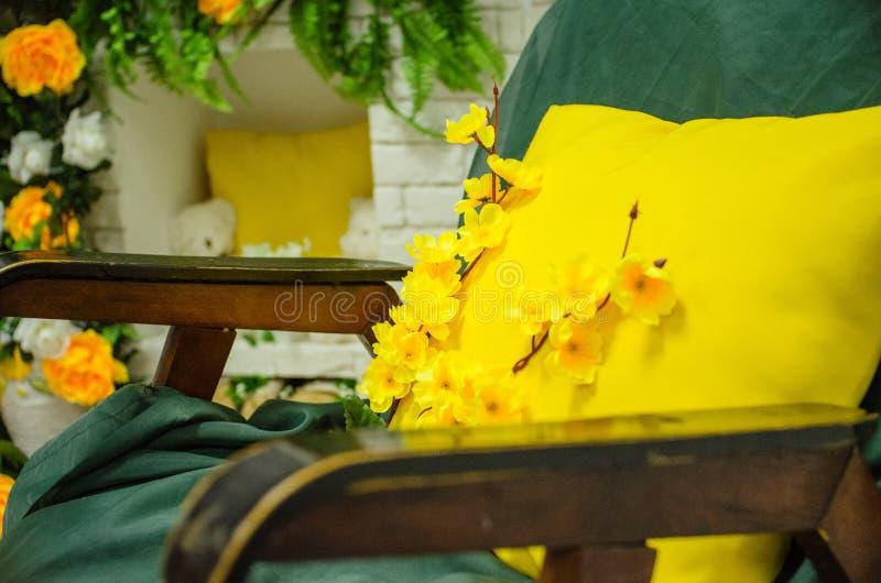 Gul kudde med blommor på bakgrunden av spisen arkivfoto
