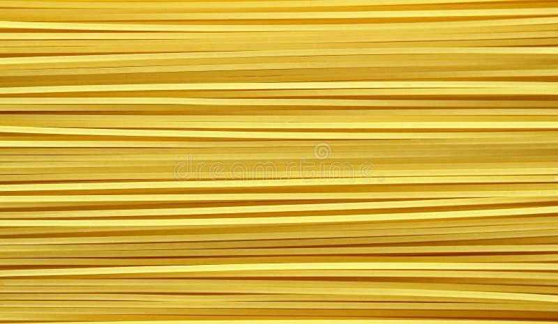 Gul lång spagetti på vit bakgrund royaltyfria bilder