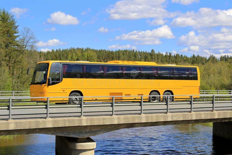 Gul lagledare Bus på den sceniska bron royaltyfri bild