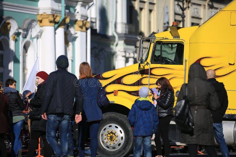 Gul lastbil och folk nära eremitboningen på en solig dag, närbild arkivbilder