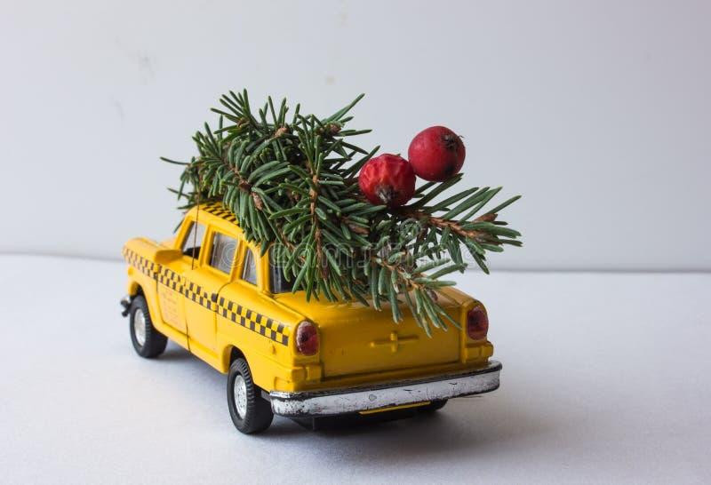 Gul leksaktaxi på en trädstam Jul arkivbilder