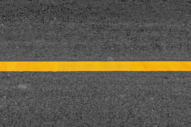 Gul linje på bakgrund för asfalttexturväg med kornigt arkivbilder