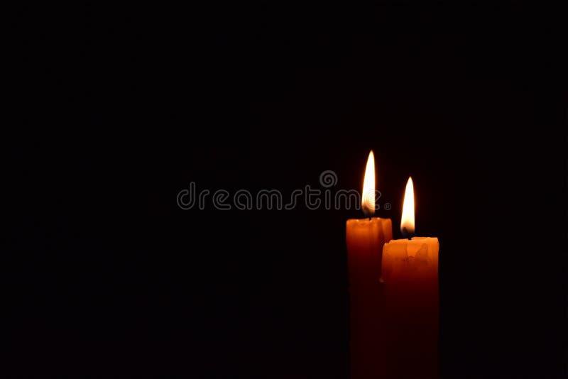 Gul ljus stearinljus som ljust bränner i den svarta bakgrunden royaltyfria foton