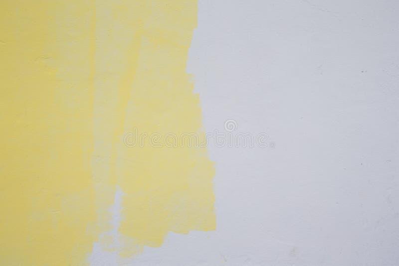 Gul målarfärgrulle på den vita väggen royaltyfri bild