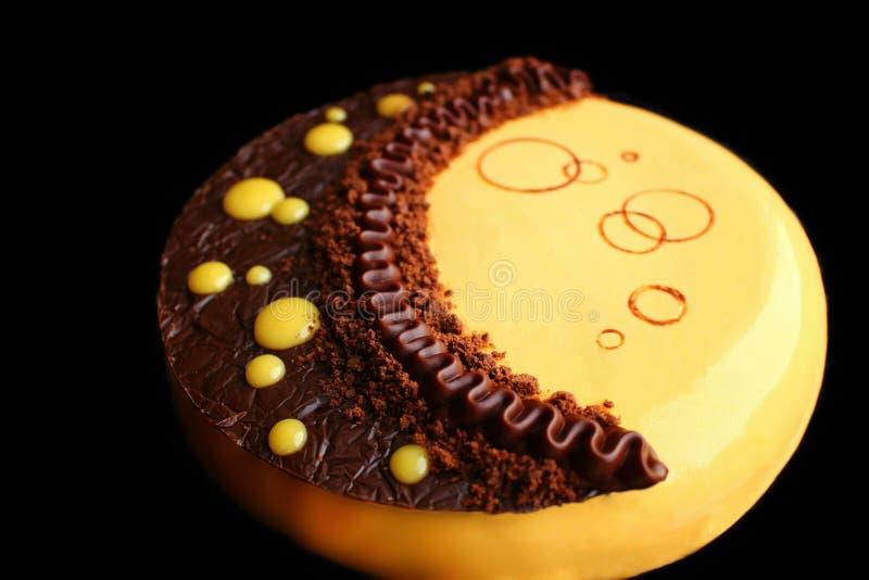 Gul månekaka med chokladganache, pumpamousse och chokladgarnering fotografering för bildbyråer