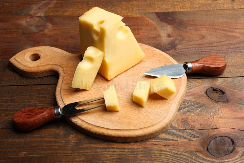 Gul Maasdam ost, kniv och gaffel för ost arkivfoto