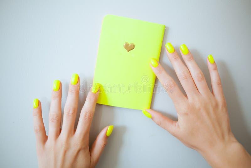 Gul moderiktig kvinnlig manikyr för neon g?r f?r att spika upp polerade produkter arkivfoto