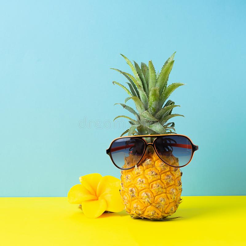 Gul mogen ananas i solglasögon på en gul blå bakgrund Rolig framsida fr?n en tropisk frukt Begrepp fotografering för bildbyråer
