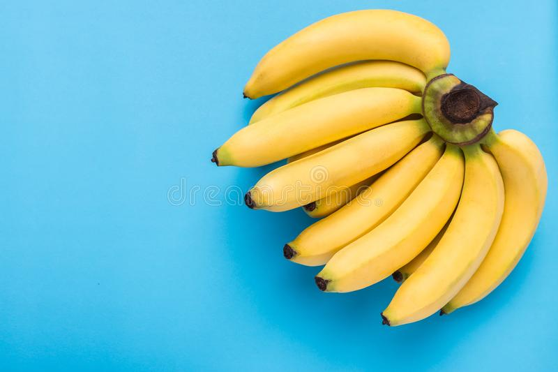 Gul mogen banan på blå bakgrund med utrymme för text eller des arkivfoto