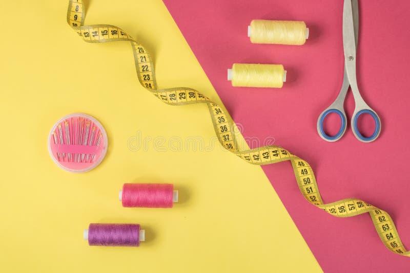 Gul och rosa bakgrund med att kontrastera sy tillförsel och tillbehör för handarbete royaltyfri foto