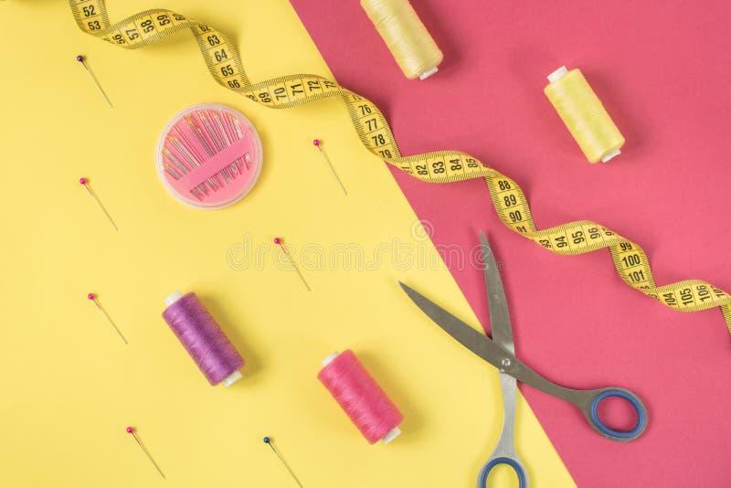 Gul och rosa bakgrund med att kontrastera sy tillförsel och tillbehör för handarbete royaltyfria bilder