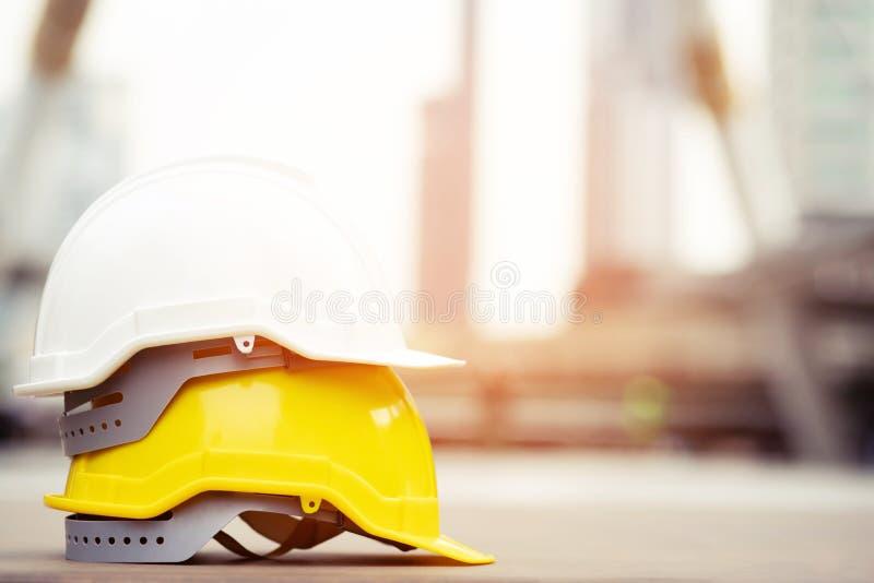 Gul och vit h?rd hatt f?r s?kerhetskl?derhj?lm i projektet p? konstruktionsplatsen arkivfoto