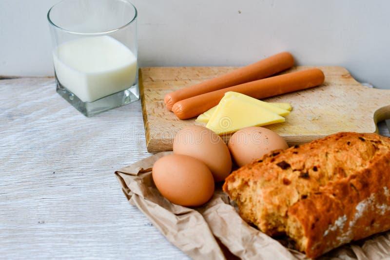 Gul ost, mjölkar, ägg bröd och korvar arkivfoton