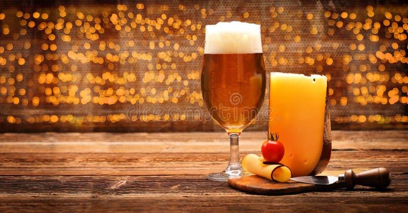 Gul ostaptitretare med öl på trätappningbakgrund arkivfoton