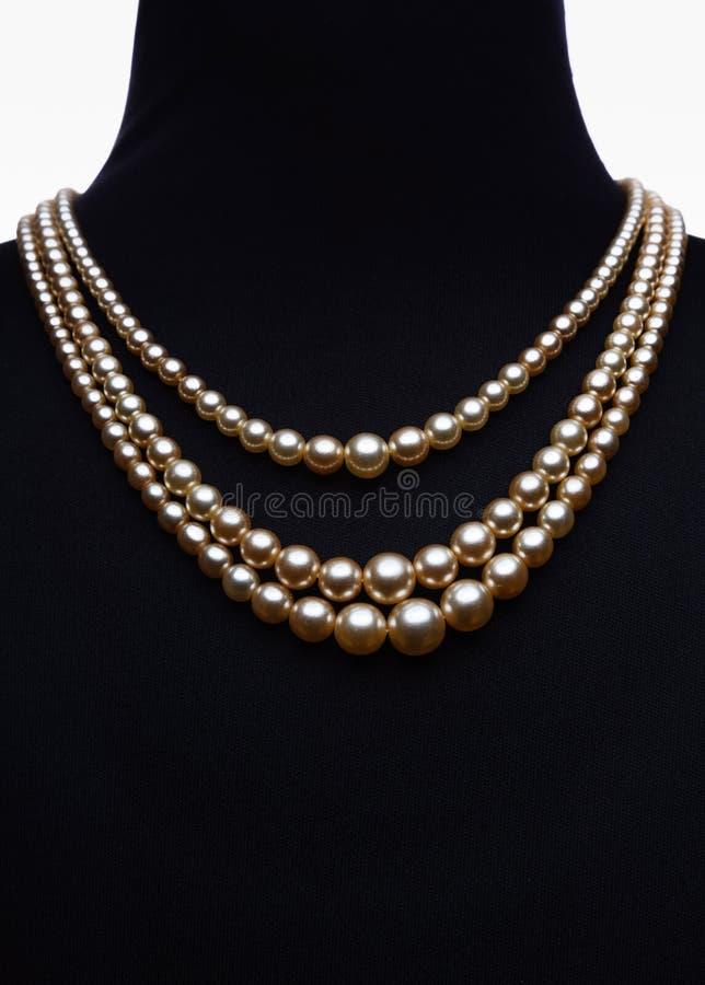 Gul pärlemorfärg halsband på den isolerade svarta skyltdockan royaltyfri fotografi