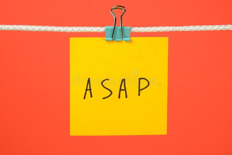 Gul pappers- anmärkning på raden med text ASAP fotografering för bildbyråer