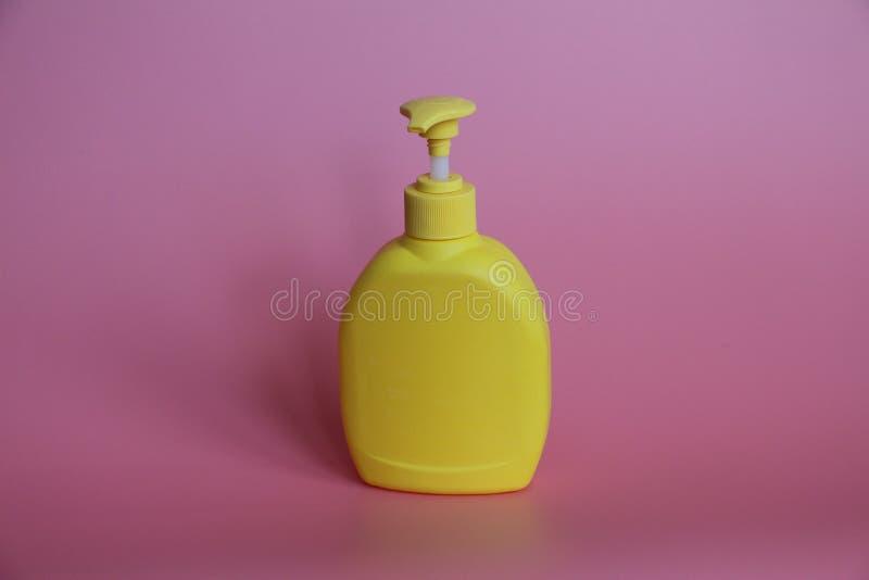 Gul plast- flaska på en rosa bakgrund Gul flaska med utmataren royaltyfri fotografi