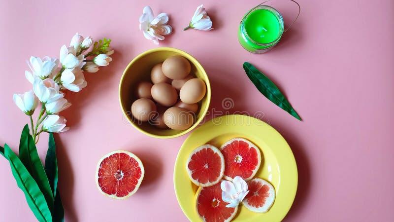 Gul platta för lycklig för påskägg röd för grapefrukter rosa vit för äpple för blommor grön stearinljus för arom på rosa bakgrund arkivfoto