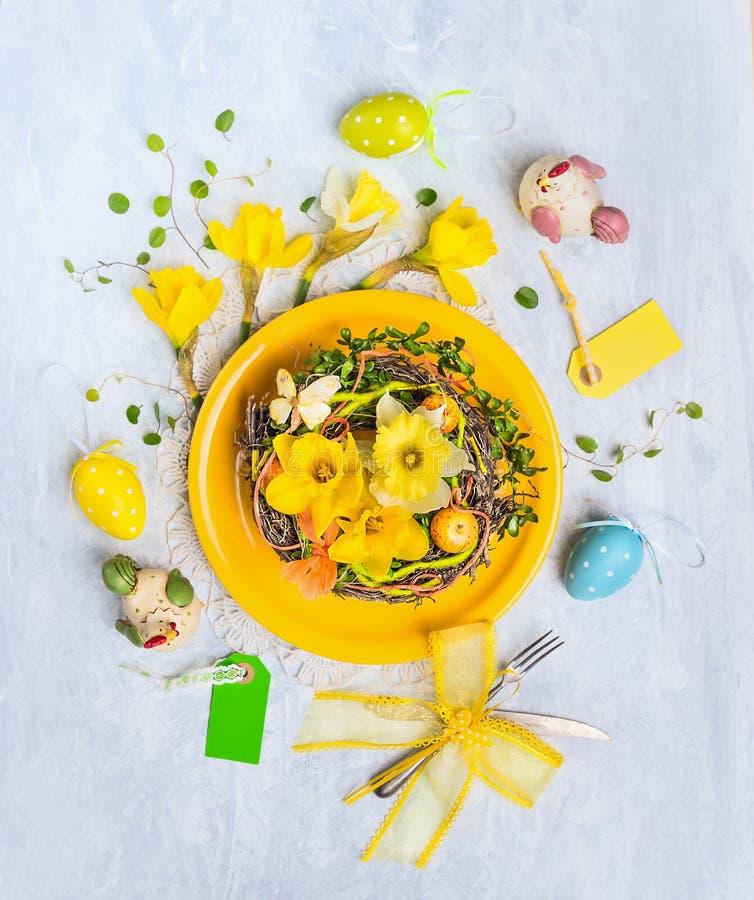Gul platta med easter ägg, rede med påskliljablommor och feriedekor royaltyfri fotografi