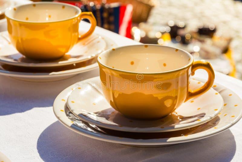 Gul polka Dot Teacup på den vita drinken för borddukTablewear kafé royaltyfria bilder